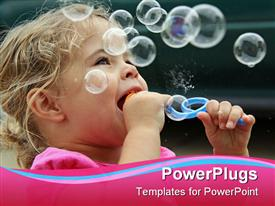 PowerPoint template displaying pretty baby girl blowing out bubbles and smiling outdoors