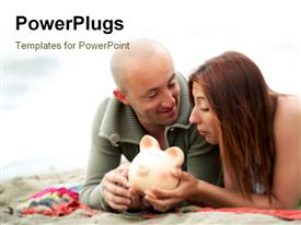 PowerPoint template displaying happy couple lay on mat with piggy bank in hand