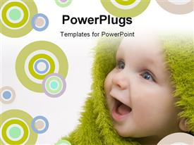 PowerPoint template displaying close up view of  a happy smiling baby wrapped with a green material