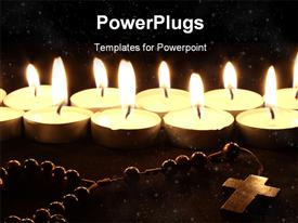 PowerPoint template displaying burning candles with crucifix on wooden desk at night