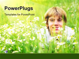 PowerPoint template displaying happy summer. A smiling young boy lying in green grass