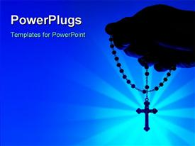 Silhouette of a hand holding rosary over blue background presentation background