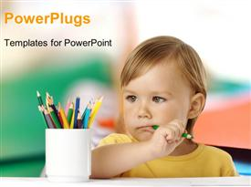 Cute child bites green crayon and thinks about new drawing ideas template for powerpoint