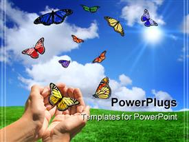 PowerPoint template displaying ten variously colored butterflies and hands that seem to release or catch butterflies on a green field and blue sky background