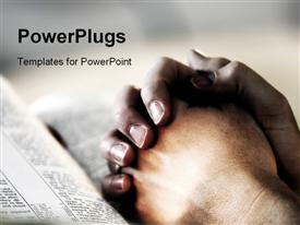 PowerPoint template displaying praying reading the bible clasped hands as a metaphor for faith