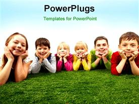 PowerPoint template displaying happy boys and girls lying on a green grass