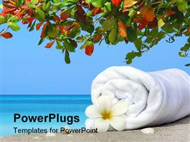 PowerPoint template displaying white rolled up towel with a flower on a tropical beach
