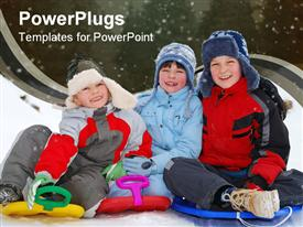 Winter portrait of three smiling children sitting on sledges on snow powerpoint theme